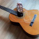 Afbeelding van een gitaar met afgebroken kop. Valt ook onder Reparatie instrumenten